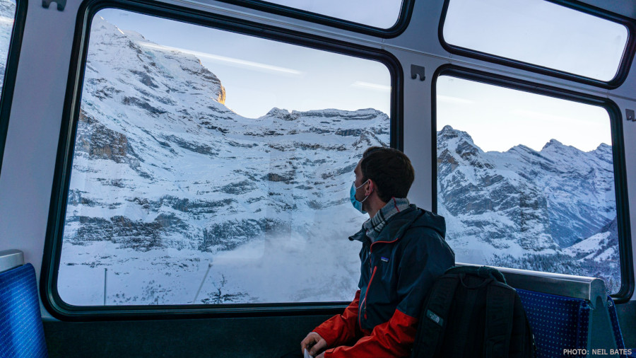 man in black jacket and red backback sitting on train window looking at snow covered mountain