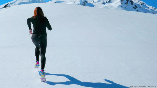 woman running up snowy mountain